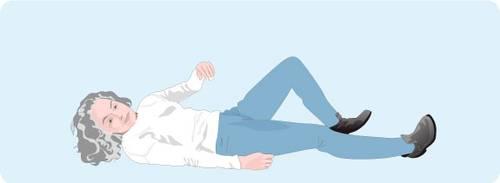 Illustration représentant l'étape 1 pour se relever après une chute: se retourner sur le ventre, en s'aidant de sa jambe la plus forte